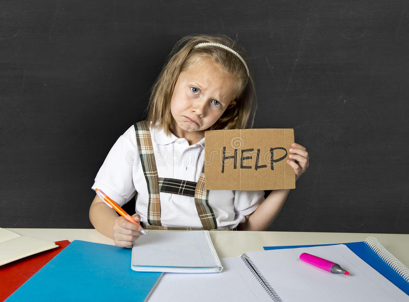 Tired cute junior schoolgirl with blond hair sitting in stress working doing homework looking bored. Sad and tired cute junior schoolgirl with blond hair sitting royalty free stock images