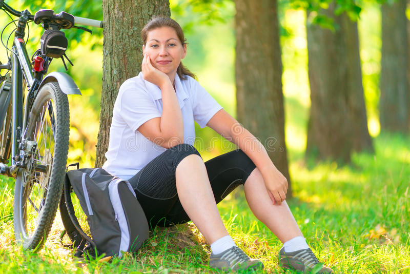 Tired cyclist resting in a park. Near a tree royalty free stock images