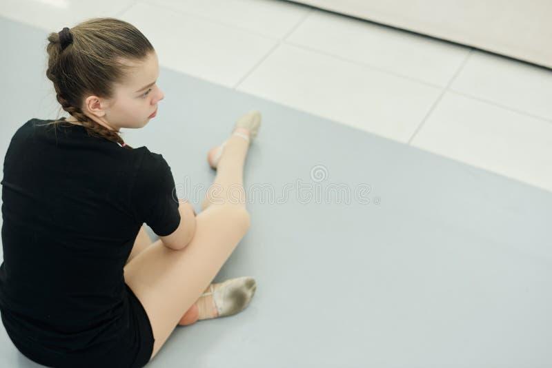 Tired dancer zit in de gym stock fotografie
