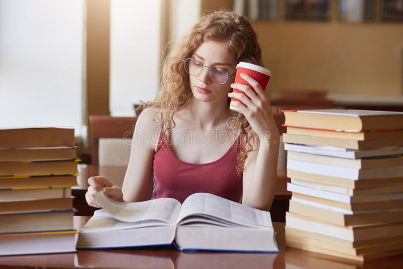 Tired determined college student searching for appropriate information for her project, reading texts, putting papercup of drink. To her head, wearing red shirt stock photography