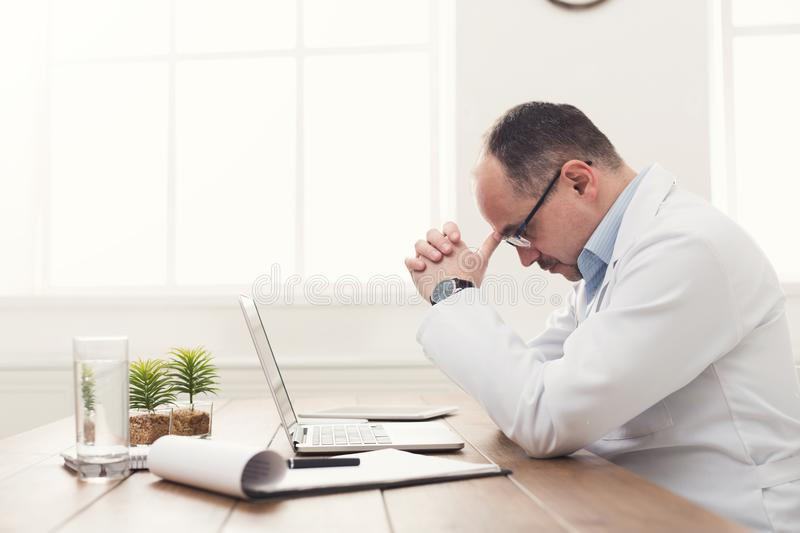 Tired doctor isitting at workplace in hospital royalty free stock photography