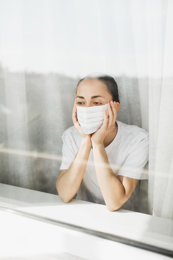 Tired doctor in mask. Important job and quarantine coronavirus pandemic. Tired doctor in medical mask looking through window. Important job and self isolation stock photography