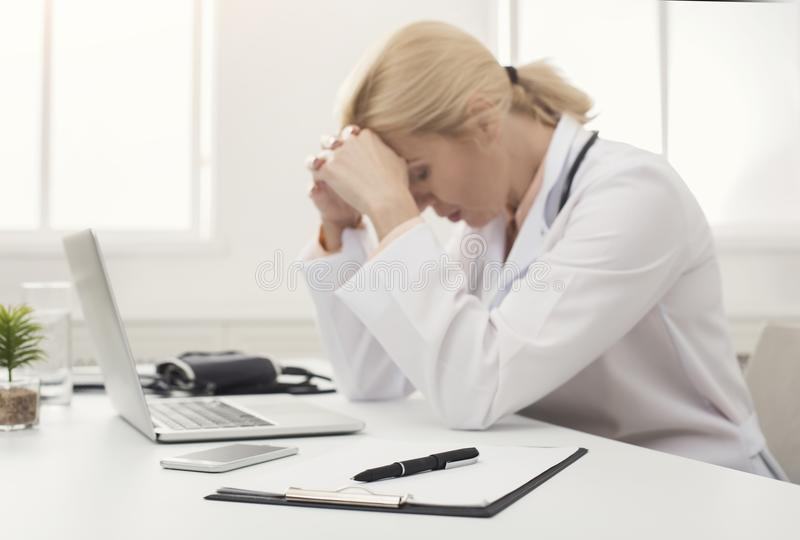 Tired doctor sitting at workplace in hospital stock image