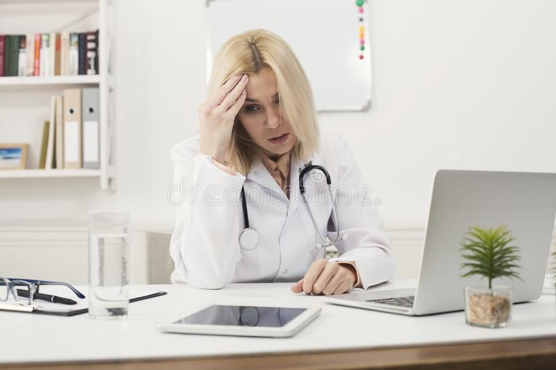 Tired doctor sitting at workplace in hospital stock photography