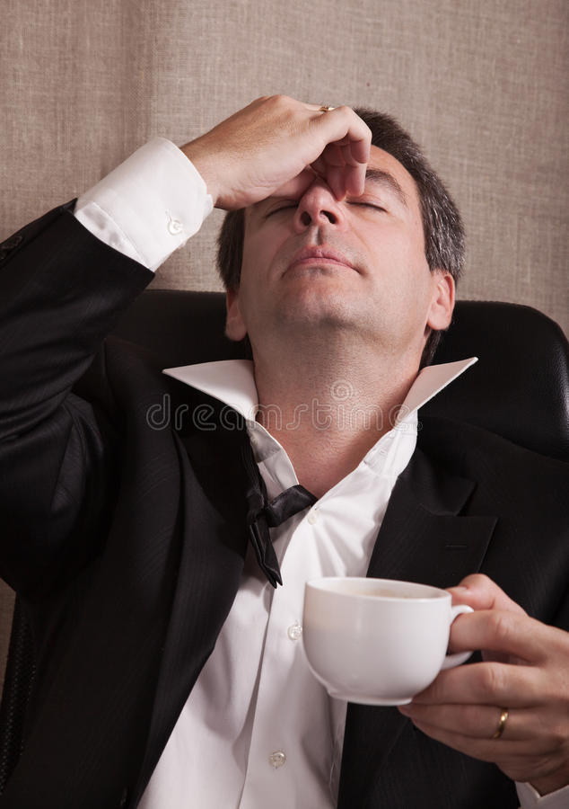 Tired dressed-up man after end of a party. With a cup of coffee royalty free stock image