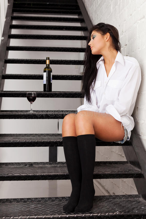 Tired of drinking. Girl sitting on stairs to nowhere stock photos
