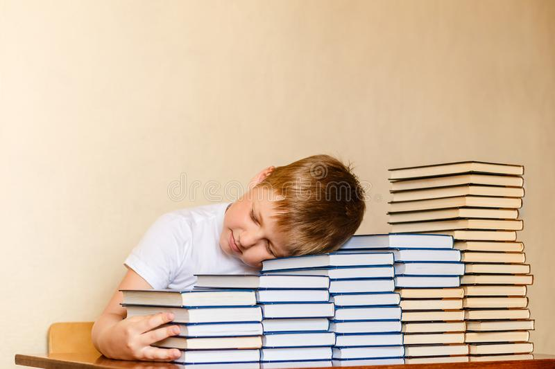 Tired eight-year-old boy sleeping on books at the table. children and reading. First-grader royalty free stock images