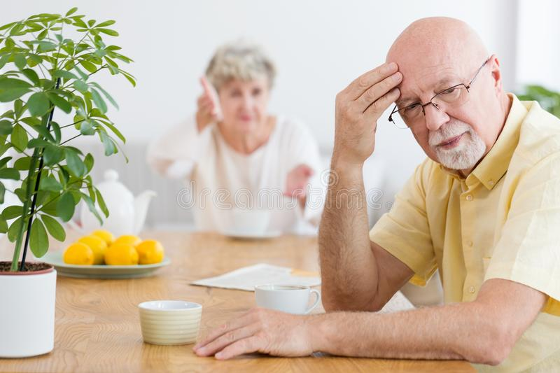 Tired elderly man arguing with his wife in the morning royalty free stock photo