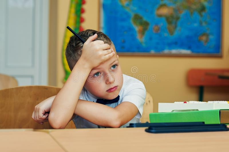 Tired elementary school kid in class royalty free stock photo