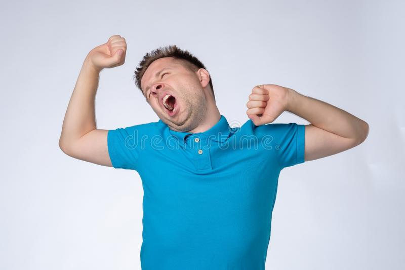 Tired european man in blue shirt feels sleepy, yawns as feels tired, opens mouth widely royalty free stock images