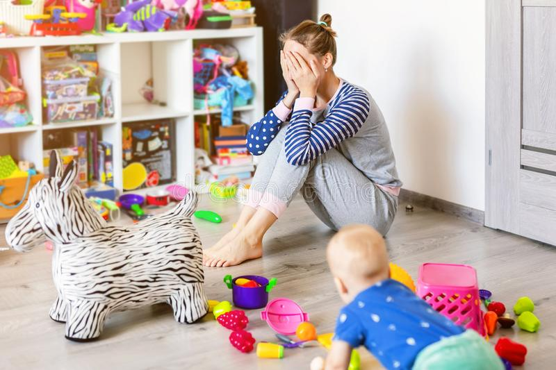 Tired of everyday household mother sitting on floor with hands on face. Kid playing in messy room. Scaterred toys and royalty free stock photos