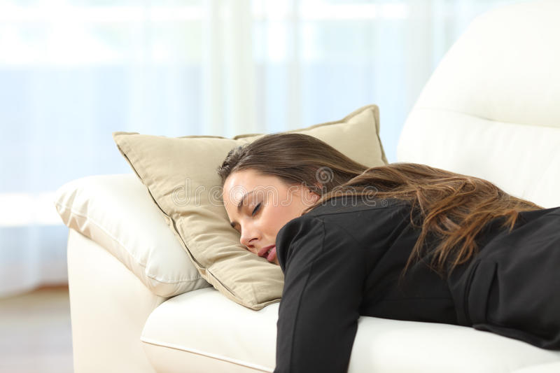 Tired executive sleeping at home after work. Tired executive sleeping lying on a sofa in the living room at home after work royalty free stock image