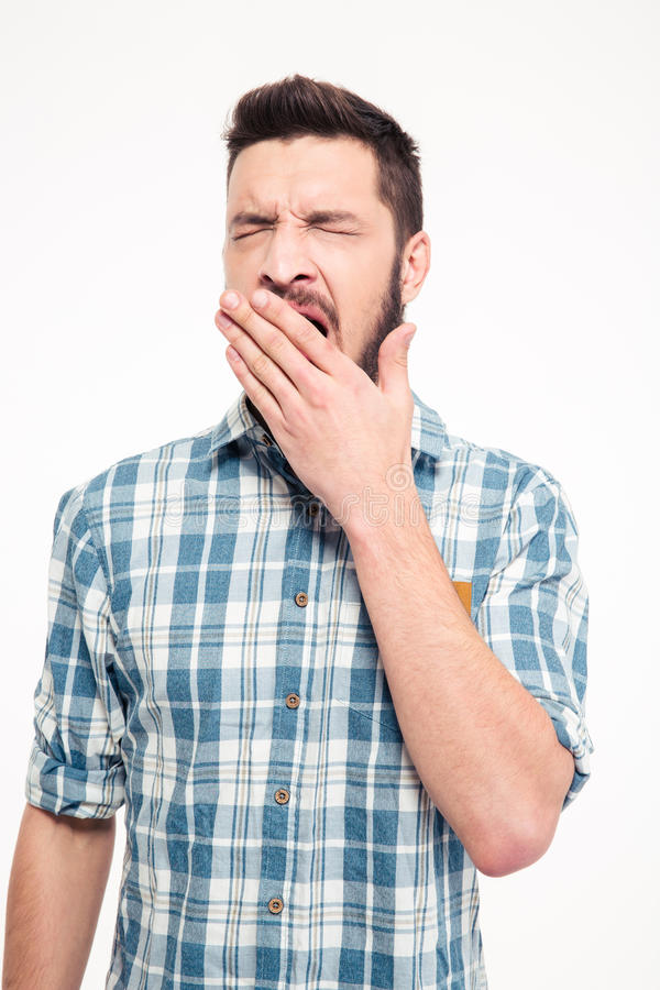 Tired exhausted bearded young man standing and yawning stock photos