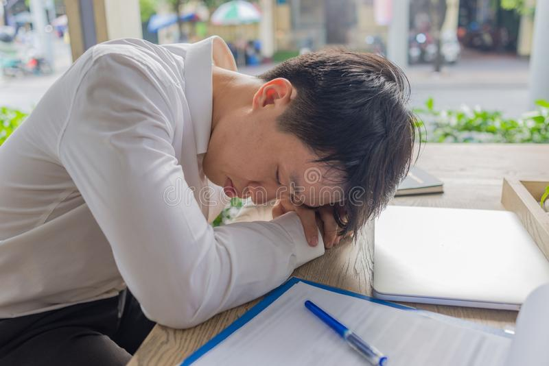 Tired and exhausted Asian businessman in white shirt sleeping. Tired and exhausted businessman in white shirt sleeping stock photography