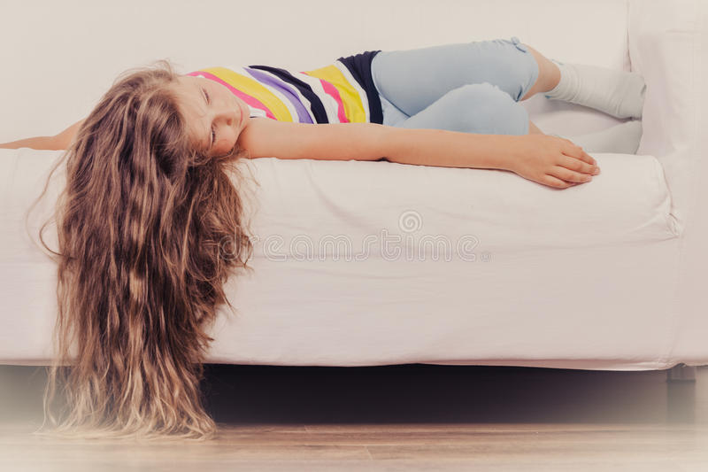Tired exhausted lazy little girl kid lying on sofa. Tired exhausted lazy little girl lying on sofa at home. Sleepy kid resting relaxing on couch royalty free stock photo