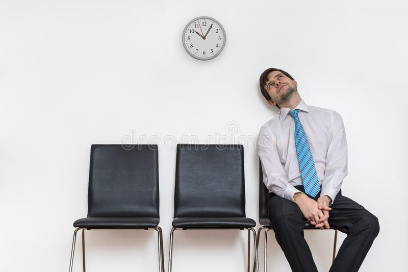 Tired and exhausted man is sitting in waiting room on chair. Tired and exhausted man is sitting in waiting room on chair royalty free stock photos