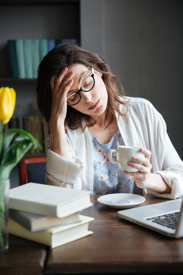 Tired exhausted mature woman in eyeglasses leaning on her hand stock photos