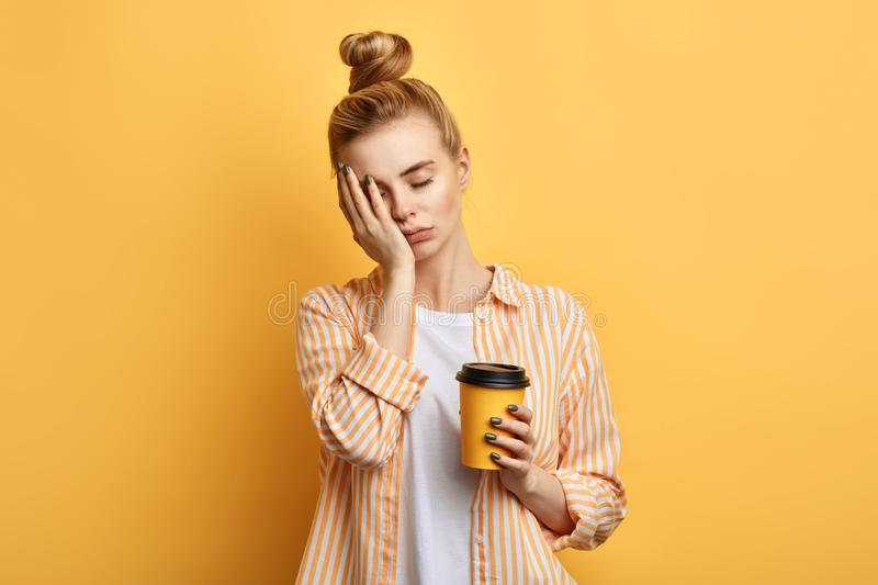 Tired fair-haired sleepy woman holds a cup of coffee stock photo