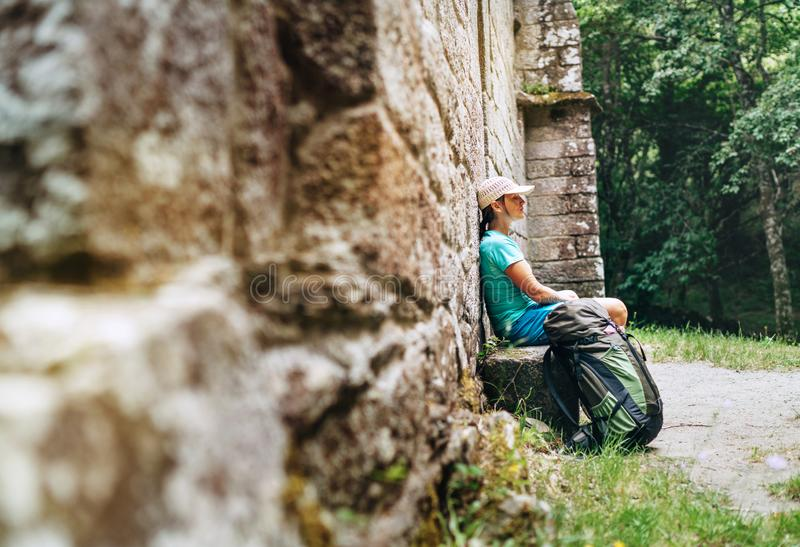 Tired female backpacker resting on the bench near the old antique brick wall castle on the famous Camino de Santiago way royalty free stock photography