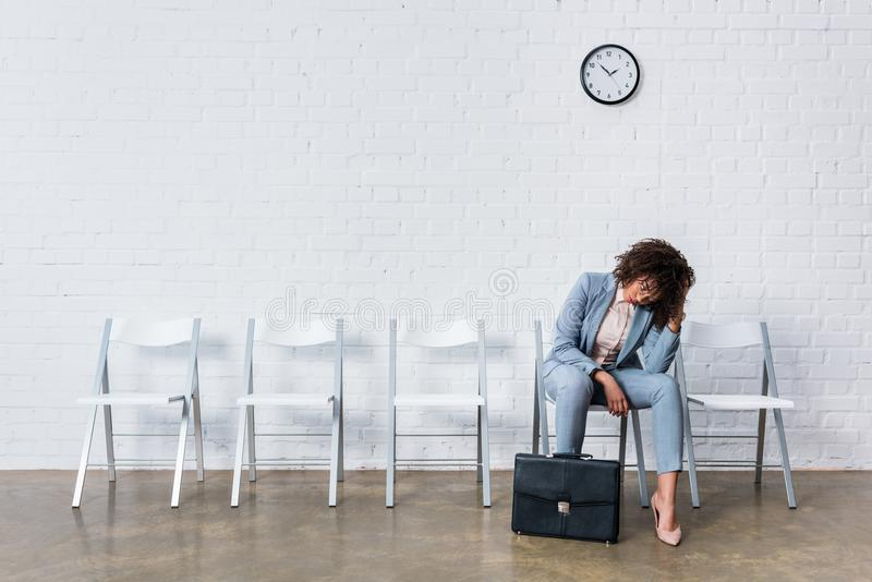 Tired female candidate with briefcase waiting stock photography