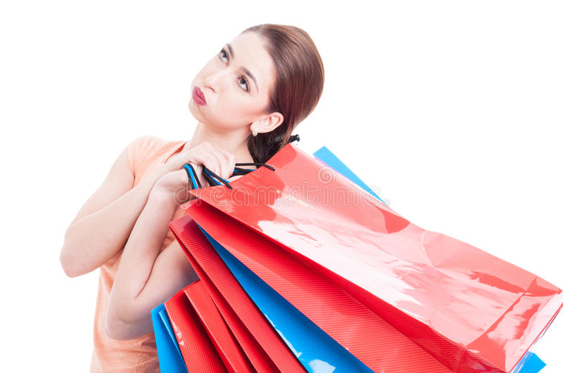 Tired female customer holding many shopping bags. And feeling exhausted isolated on white background royalty free stock images