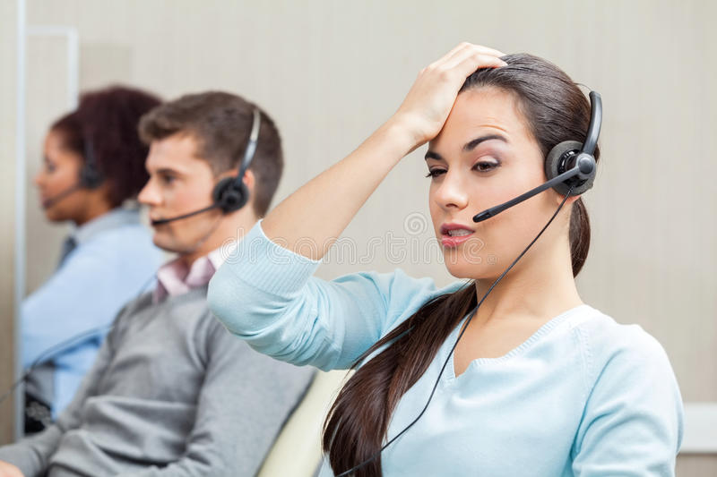 Tired Female Customer Service Representative In. Tired female customer service representative with colleagues in background at call center royalty free stock photo