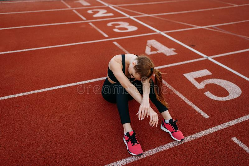 Tired female jogger sitting on the ground, stadium. Tired female jogger sitting on the ground, training on stadium. Woman doing stretching exercise before royalty free stock images