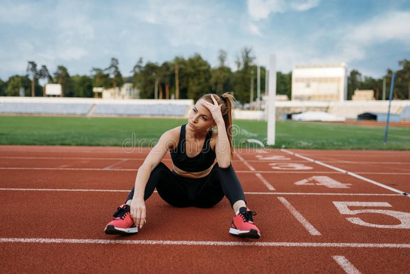Tired female jogger sitting on the ground, stadium. Tired female jogger sitting on the ground, training on stadium. Woman doing stretching exercise before stock images