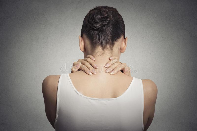 Tired female massaging her painful neck stock photo