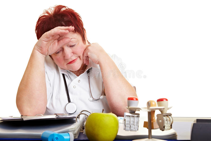 Tired female physician with burnout. Syndrome sitting at her desk royalty free stock images