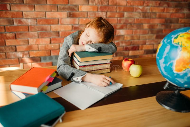 Tired female pupil asleep on stack of textbooks stock photography