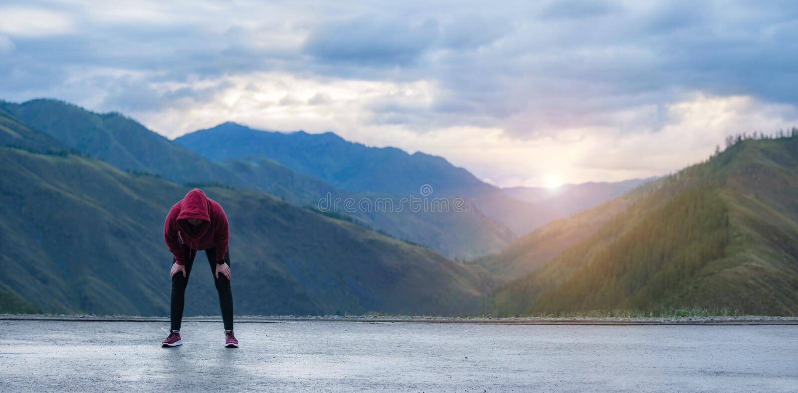 Tired female runner taking a rest after running hard in mountain road. Sweaty athlete after marathon training in road royalty free stock photo