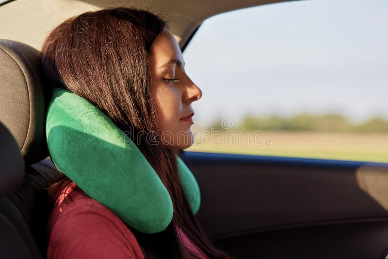 Tired female traveller uses travel pillow, sleeps in car, covers long distance, feels comfort for neck, has long dark hair, closes royalty free stock photo