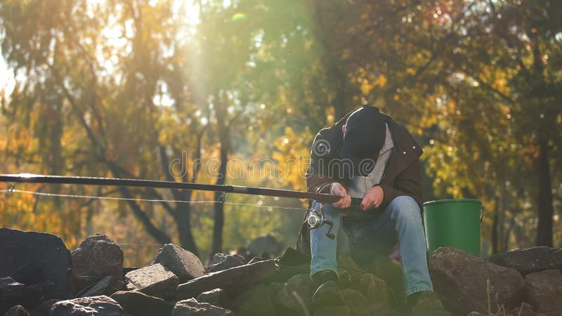 Tired fisherman falling asleep while fishing, long day outdoors, exhaustion. Stock photo royalty free stock photography