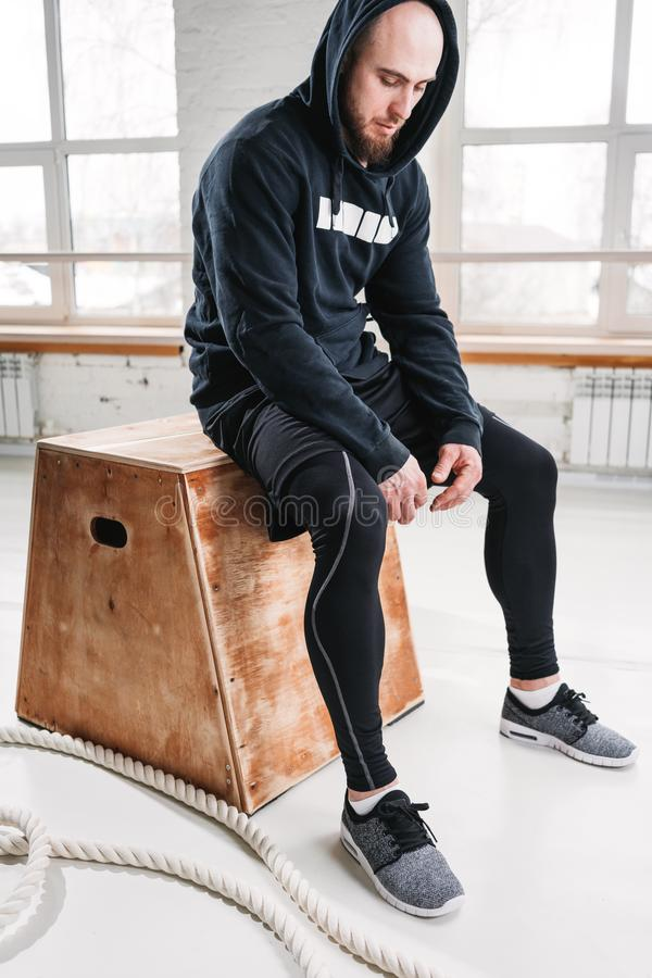 Tired fit man wearing black hoodie sitting on box at light hall royalty free stock photos