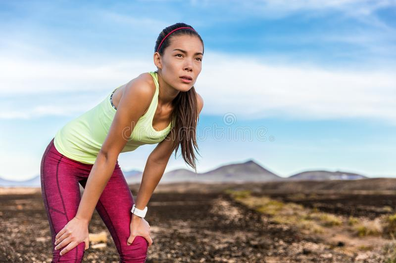 Tired focus and determination trail running woman. Tired trail running woman looking at mountain landscape nature path with focus and determination to take on royalty free stock photos