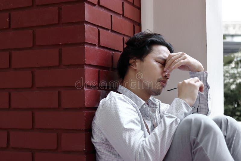Tired forçou o sentimento asiático novo do homem de negócio decepcionado ou esgotado com trabalho no escritório exterior fotos de stock