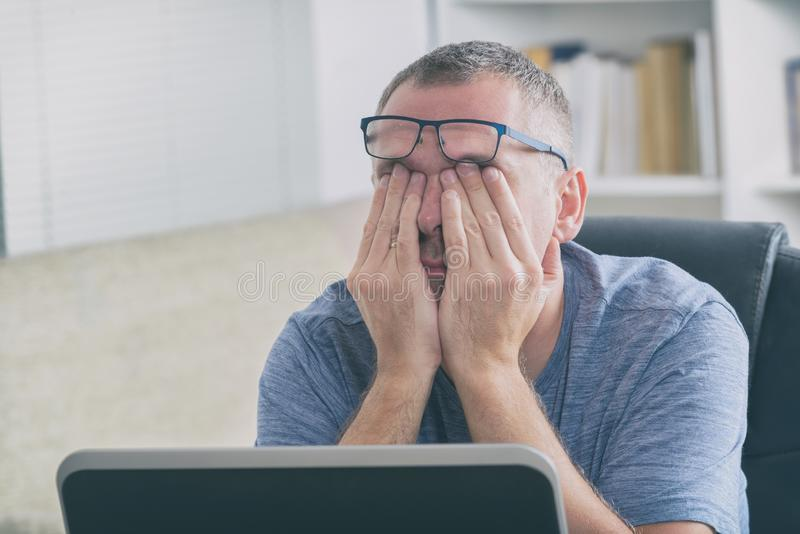 Tired freelancer man rubbing his eye royalty free stock photography