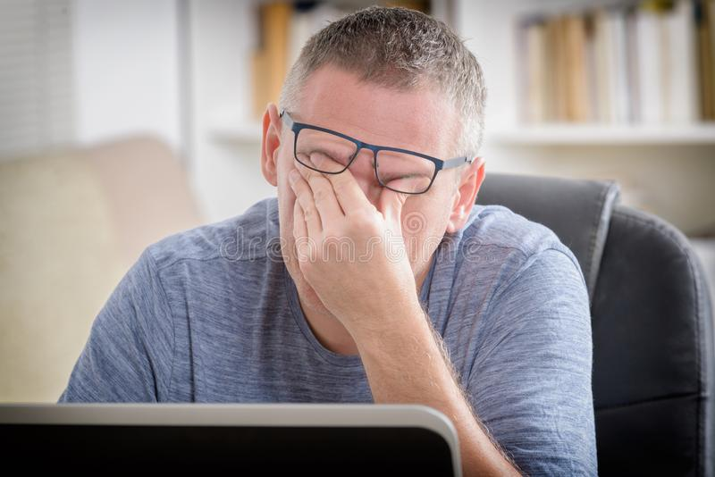Tired freelancer man rubbing his eye. While working with laptop stock photos