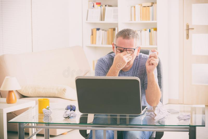 Tired freelancer man rubbing his eyes. While working with laptop stock photography