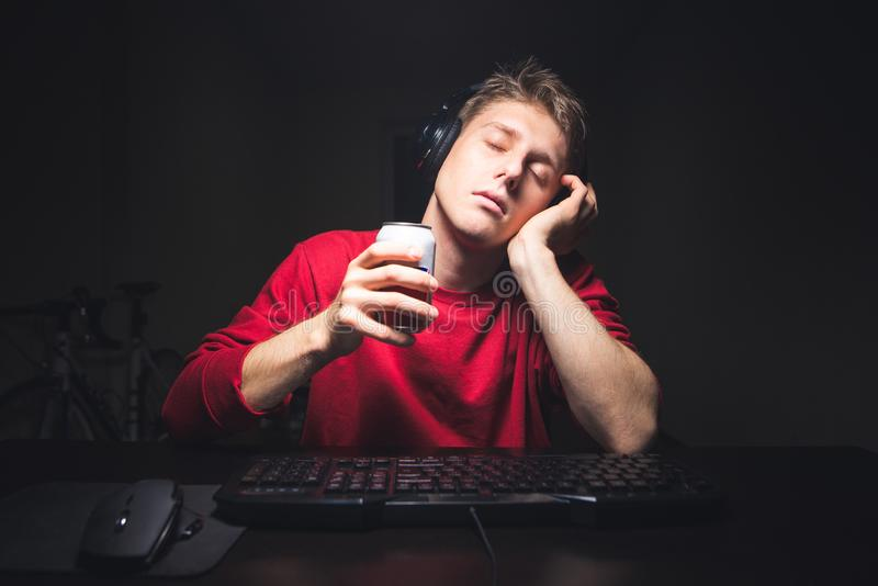 Man sitting at home near a computer with a can of drinks in the hands and sleeping. Tired gamer in the headphones sleeps near the computer. Young man sitting at royalty free stock photo