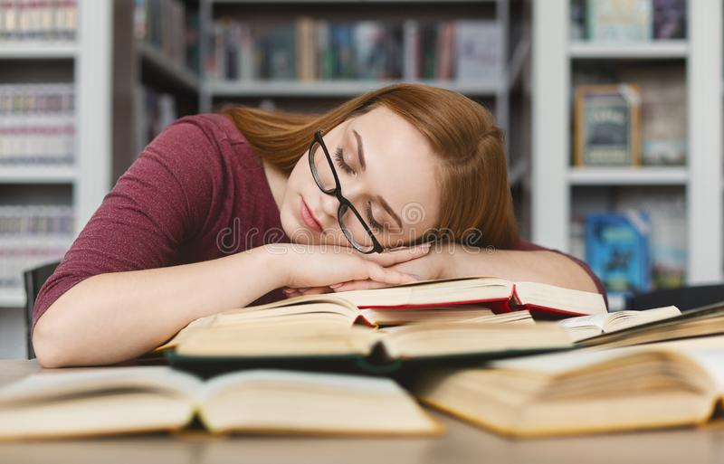 Tired girl with glasses having nap on books in library stock image
