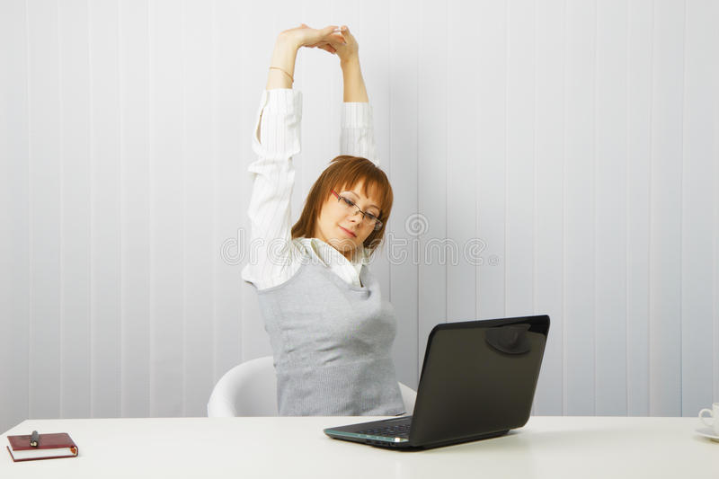 Tired girl with a laptop stretches royalty free stock photography
