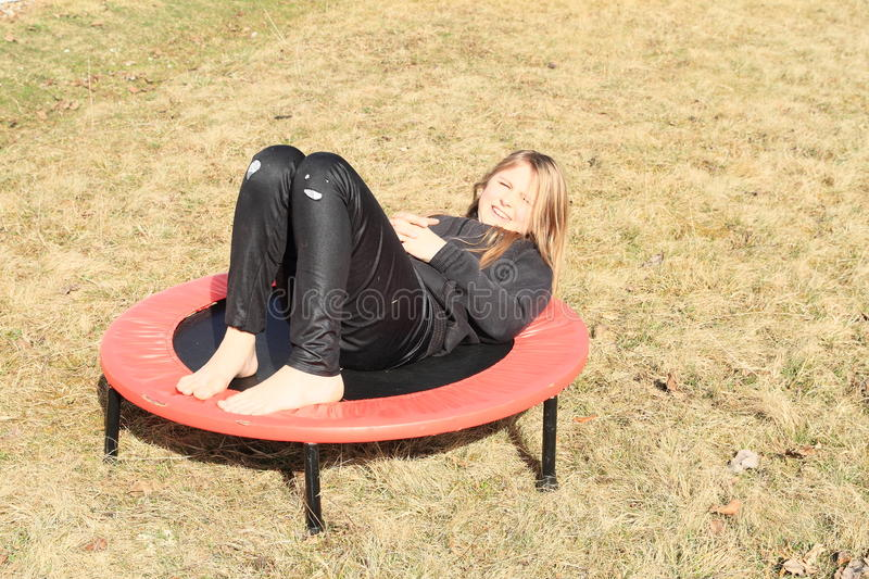 Tired girl lying on trampoline royalty free stock images