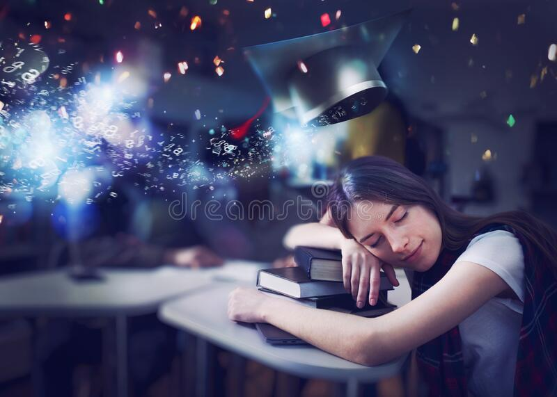 Tired girl sleeps over books and dreams of graduating. Concept of graduation and determination stock photo