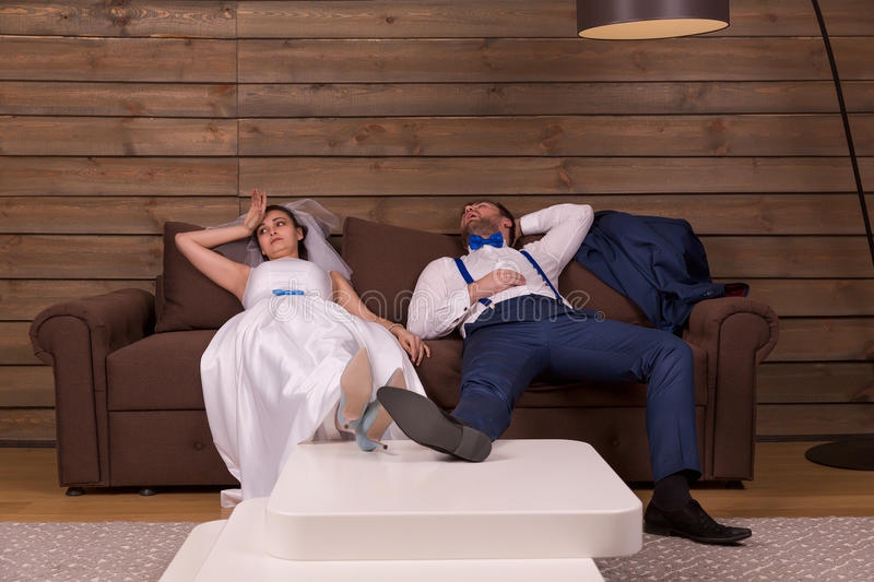 Tired groom and bride relax on couch royalty free stock photography