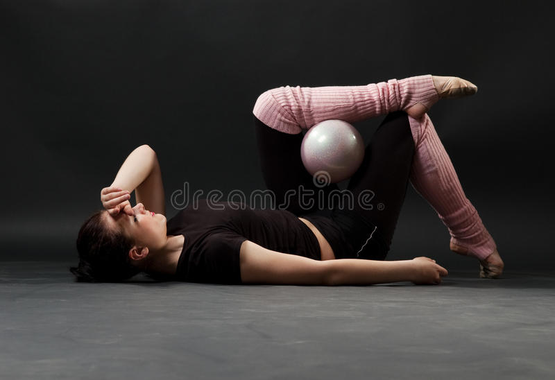 Tired gymnast with ball. Resting on the floor royalty free stock photos