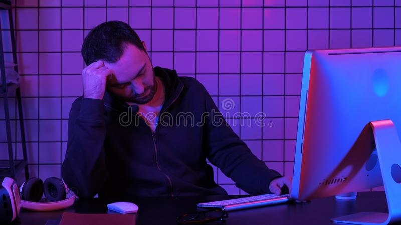 Tired hacker sleeping near computer while computer processing. Professional shot in 4K resolution. 020. You can use it e.g. in your commercial video, medical stock images