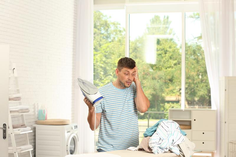 Tired handsome man with iron and clean laundry near board. At home royalty free stock images