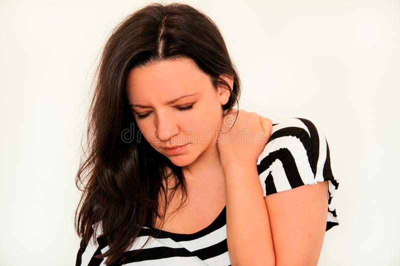 Tired handsome woman having pain in neck, rubbing it royalty free stock photo